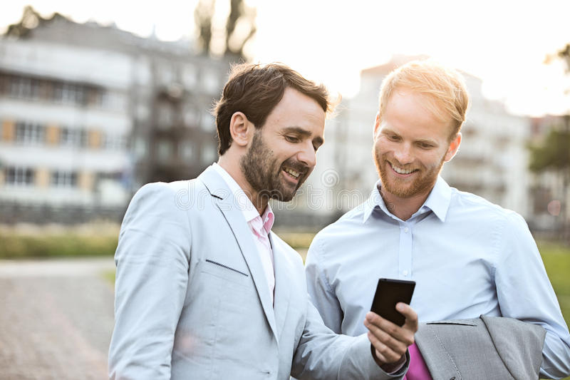 使用手机的愉快的商人在城市 免版税库存图片