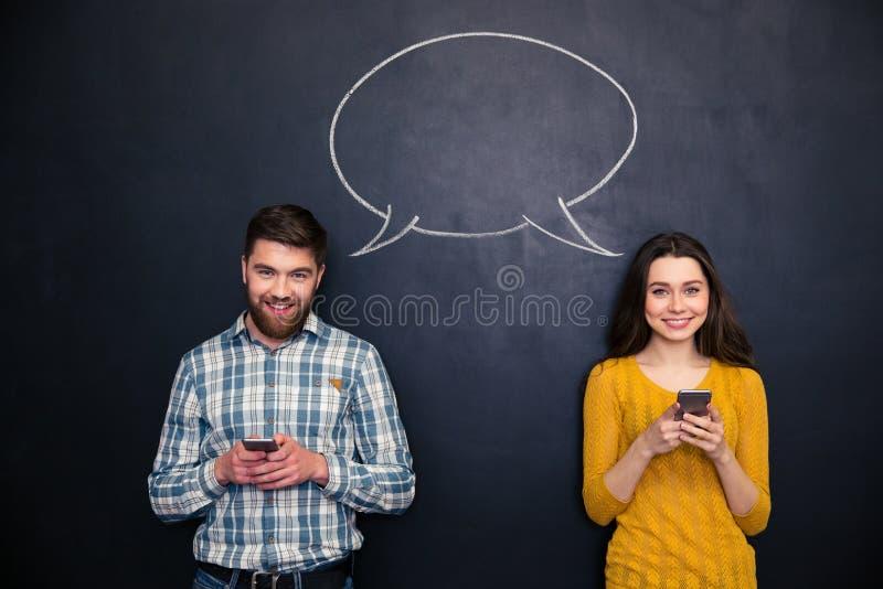使用手机的愉快的夫妇在有讲话的黑板起泡 图库摄影