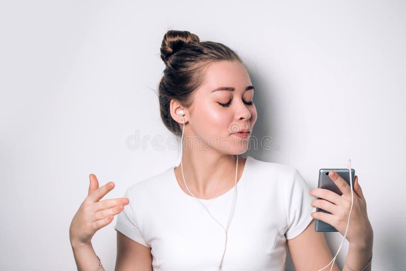使用手机的愉快的少妇,当听到在智能手机时的音乐 图库摄影