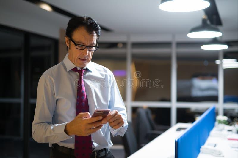 使用手机的成熟商人在办公室在晚上 免版税库存图片