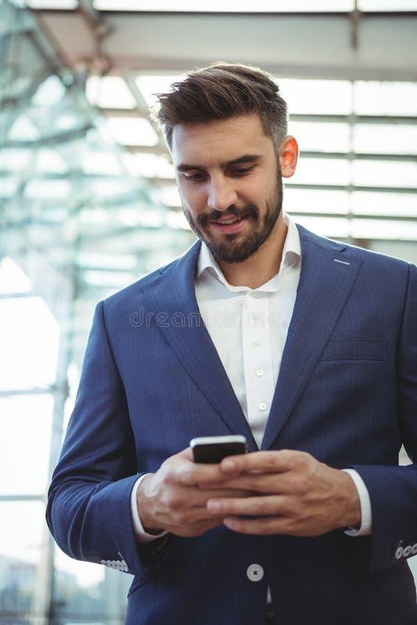 使用手机的殷勤商人 免版税库存图片
