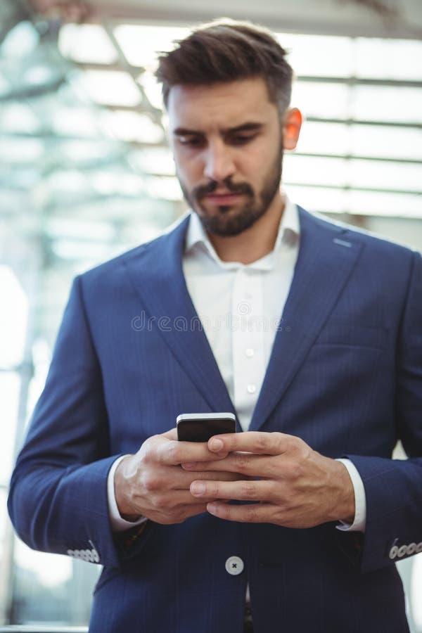 使用手机的殷勤商人 库存照片