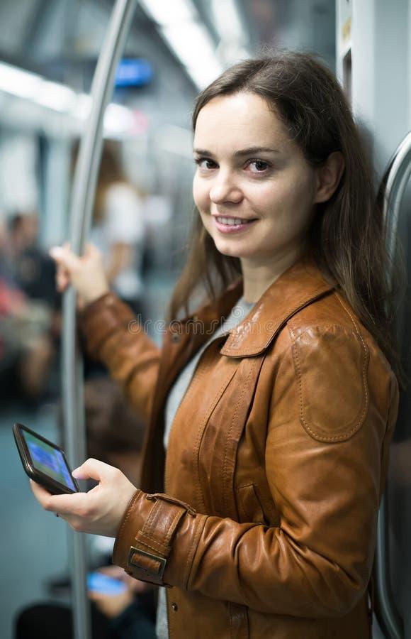 使用手机的深色的女孩和微笑对地铁 库存图片