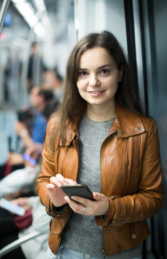 使用手机的深色的女孩和微笑对地铁 图库摄影