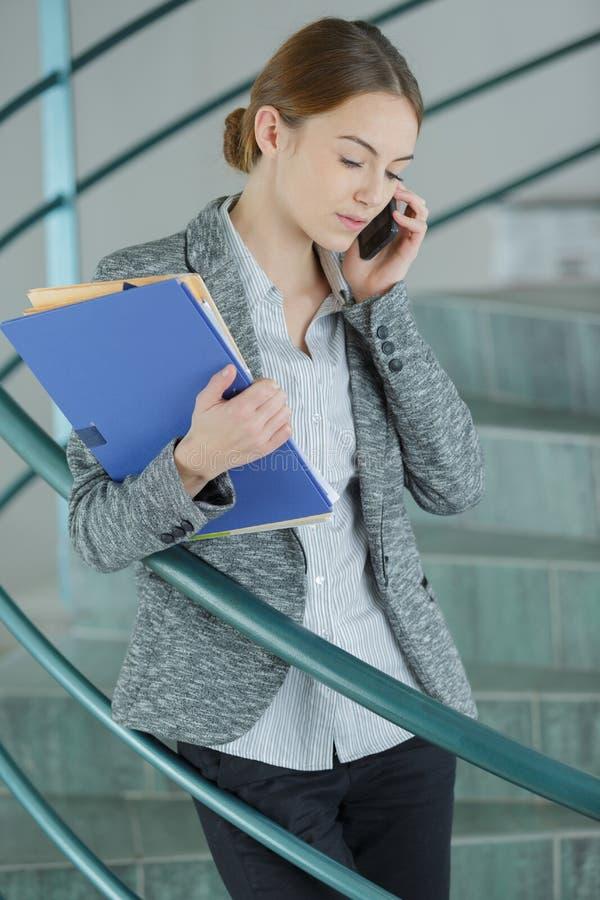 使用手机的熟练的女工 免版税库存图片