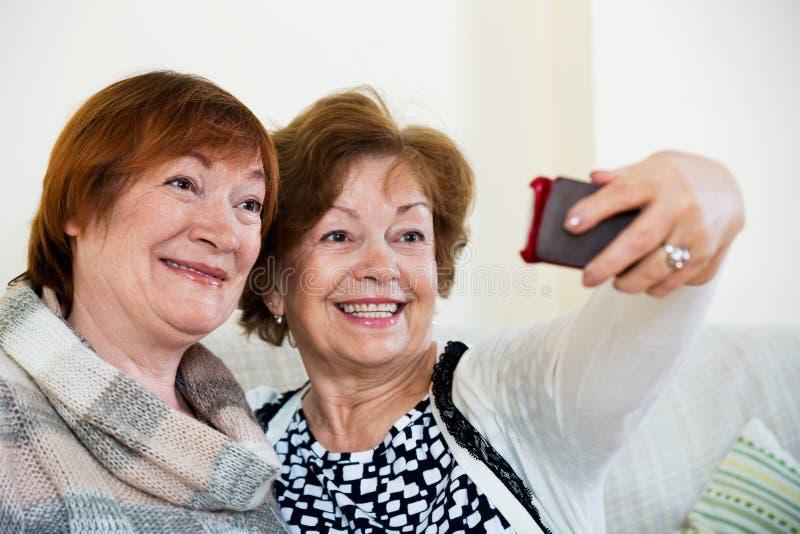 使用手机的现代微笑的成熟妇女 图库摄影
