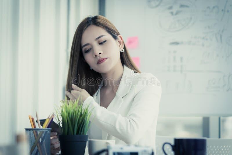 使用手机的疲乏的办公室妇女检查她的秀丽和头发 免版税库存照片