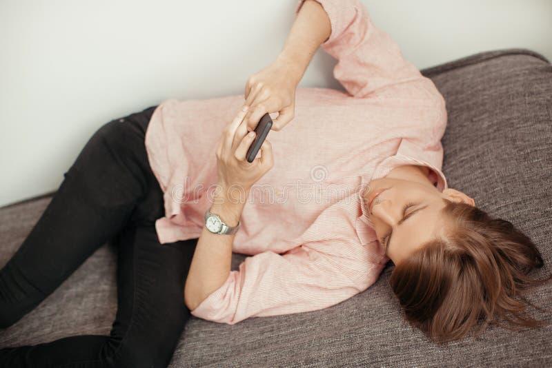 使用手机的白种人年轻人,当说谎室内时 对应,聊天或浏览 浏览的概念,休息 库存照片