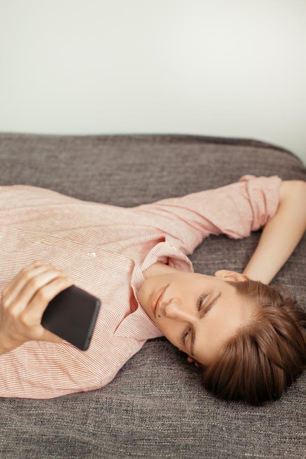 使用手机的白种人年轻人,当说谎室内时 对应,聊天或浏览 浏览的概念,休息 免版税库存照片