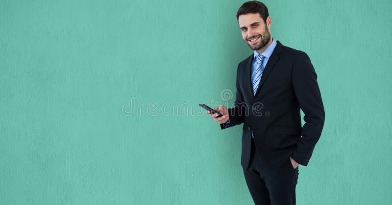 使用手机的确信的商人在绿色背景 免版税库存图片