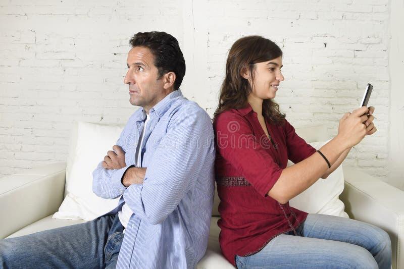 使用手机的社会网络上瘾者妇女忽略丈夫或男朋友翻倒和恼怒 库存照片