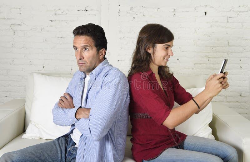 使用手机的社会网络上瘾者妇女忽略丈夫或男朋友翻倒和恼怒 免版税库存图片