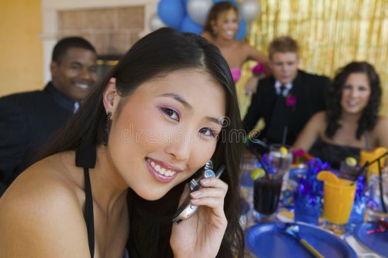 使用手机的穿着体面的少年女孩在学校舞蹈 库存图片