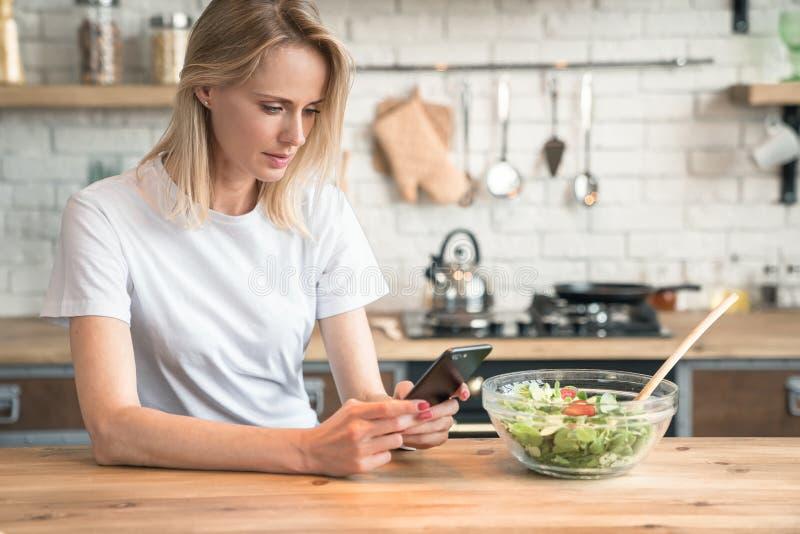 使用手机的美丽的年轻女人,当做沙拉在厨房时 r E ?? r 库存照片
