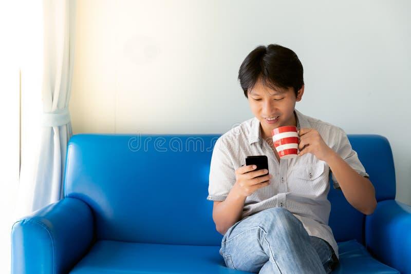 使用手机的英俊的亚裔人,当喝一些咖啡和坐沙发时 库存图片
