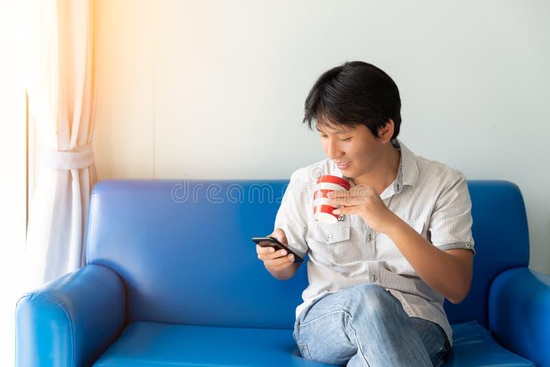 使用手机的英俊的亚裔人,当喝一些咖啡和坐蓝色沙发时 图库摄影