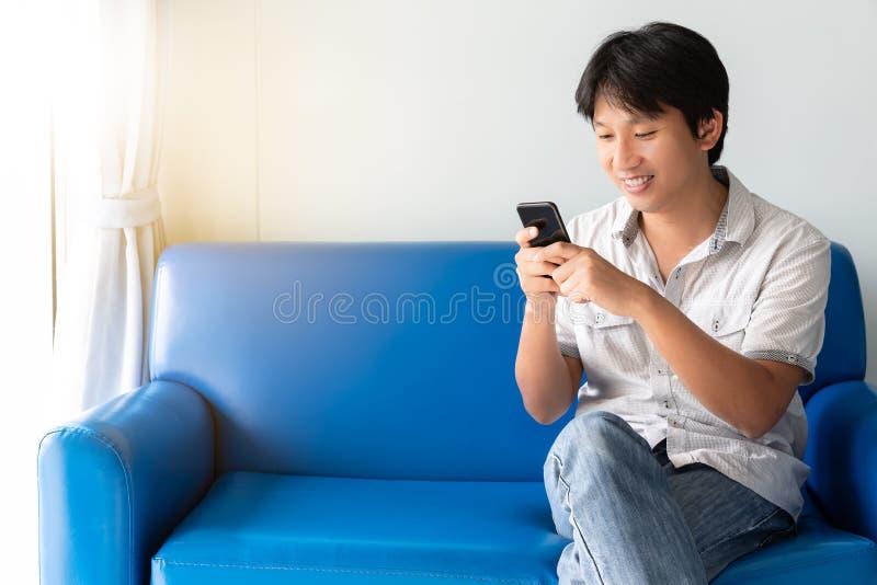 使用手机的英俊的亚裔人,当坐蓝色沙发时 免版税图库摄影