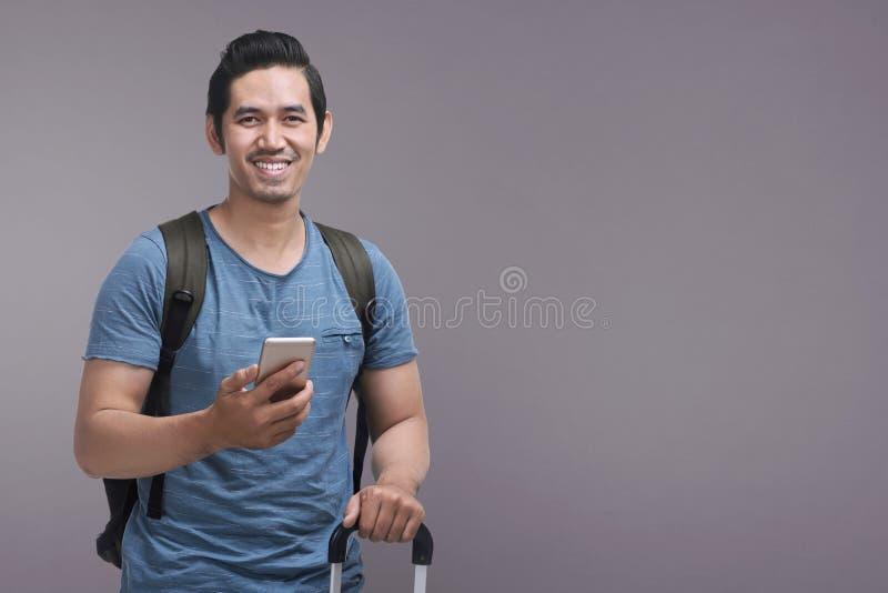 使用手机的英俊的亚裔人,当拿着手提箱时 库存照片