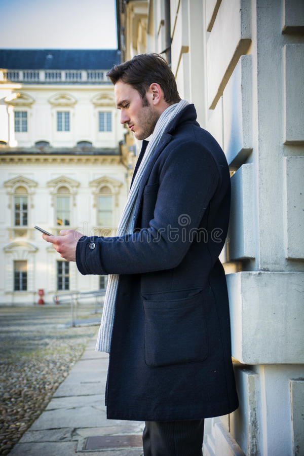 使用手机的英俊的时髦人键入文本,室外 库存图片