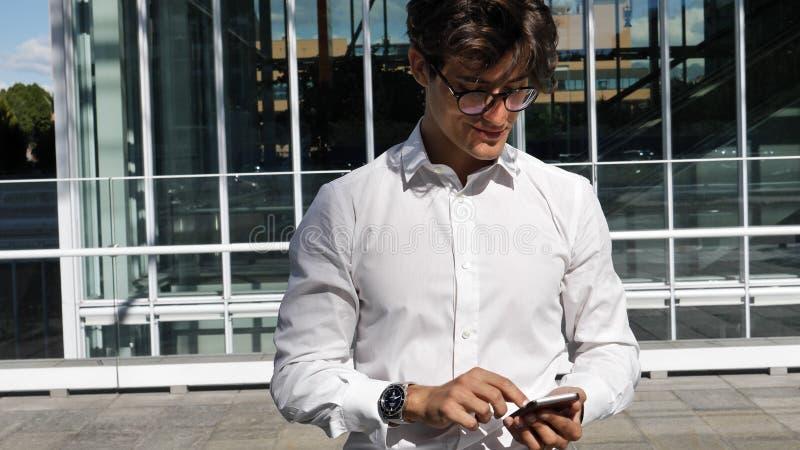 使用手机的英俊的时髦人键入文本 免版税库存照片