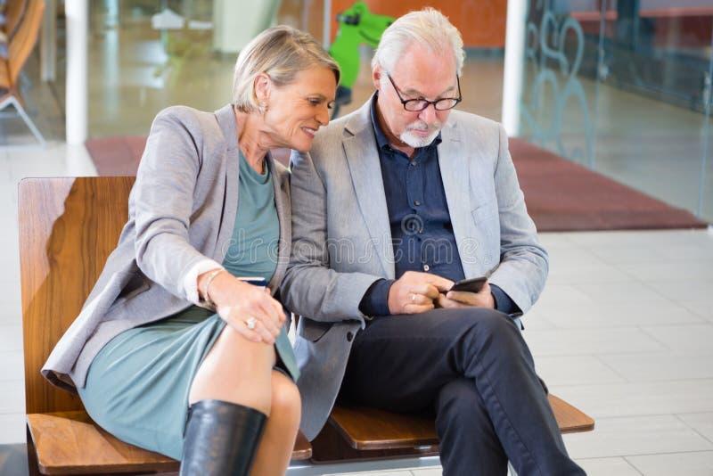 使用手机的资深企业夫妇在机场等待是 免版税库存照片