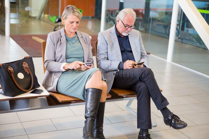 使用手机的资深企业夫妇在等待Ar的机场 库存图片