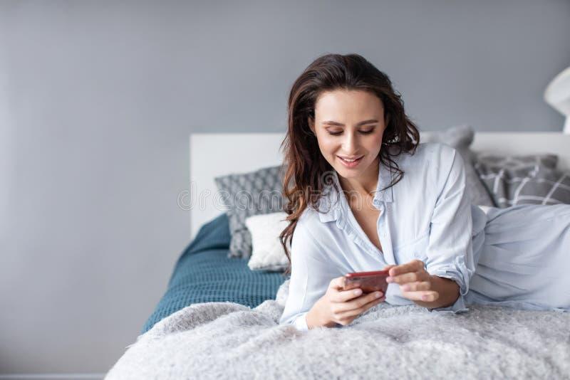 使用手机的迷人的妇女,当在家说谎在舒适床早晨时 库存照片