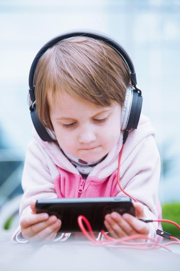 使用手机的逗人喜爱的儿童女孩观看网上电子教学录影对学习英语 学会到处和任何时候是 免版税库存图片