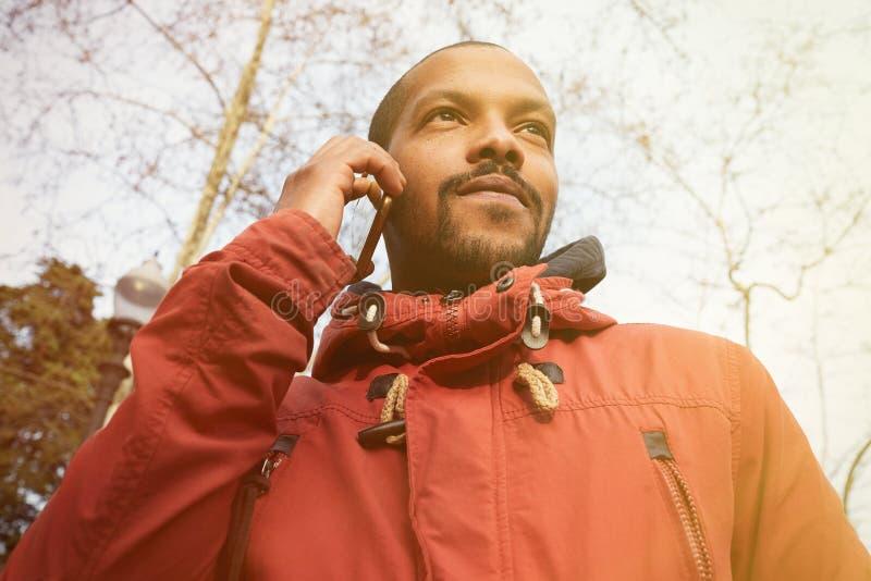 使用手机的非裔美国人的人在公园 穿不拘形式的衣裳的年轻愉快的微笑的都市行家人和 免版税库存图片