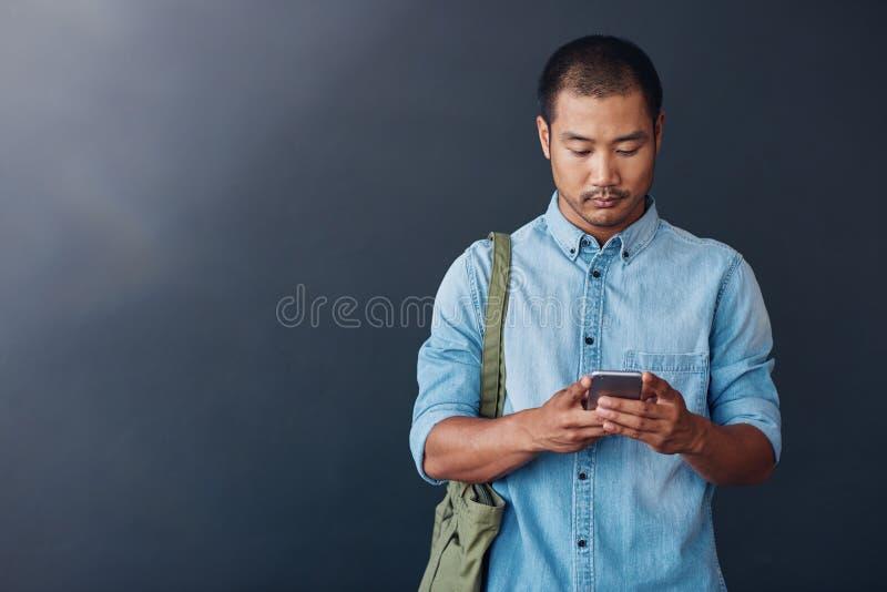 使用手机的年轻亚裔设计师在一个现代办公室 免版税图库摄影
