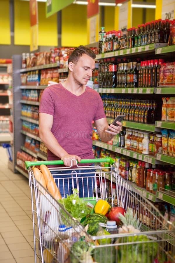 使用手机的年轻人在超级市场 免版税图库摄影