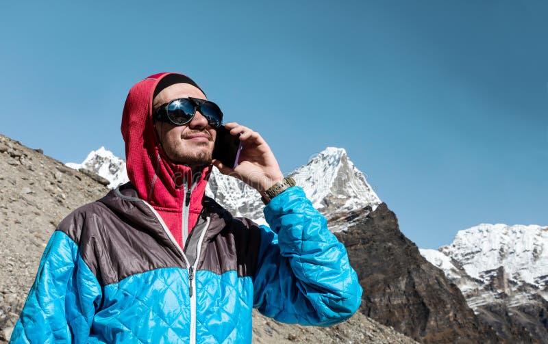 使用手机的年轻人在遥远的高处山 库存图片