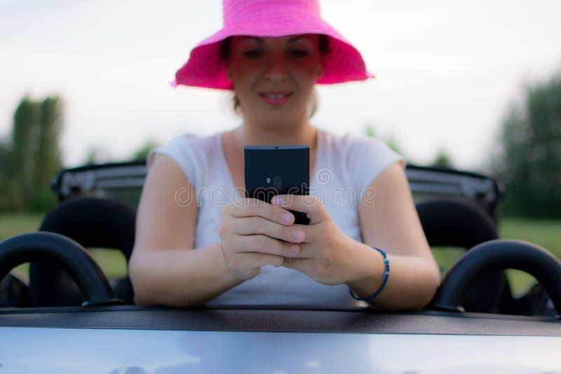 使用手机的年轻可爱的女孩在她的汽车 库存照片