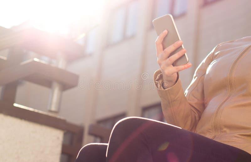 使用手机的轻松的女孩在阳光 有接触智能手机和变冷的时髦衣裳的时髦的少妇 库存图片