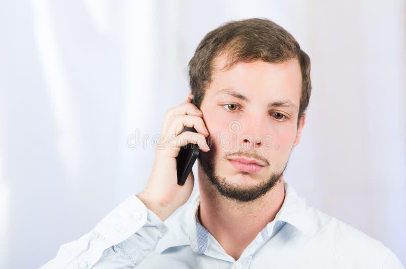 使用手机的年轻英俊的人 库存照片