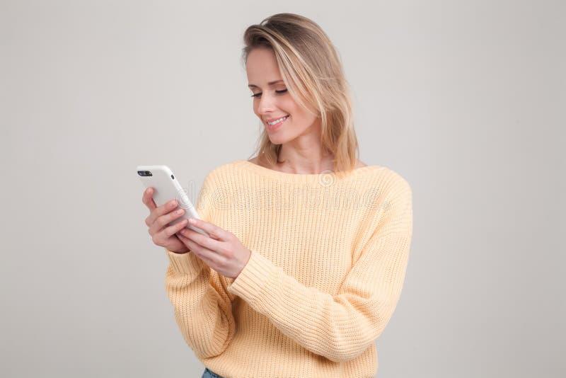 使用手机,传讯的年轻白肤金发的微笑的妇女画象,是愉快与她的男朋友聊天 r 免版税库存图片