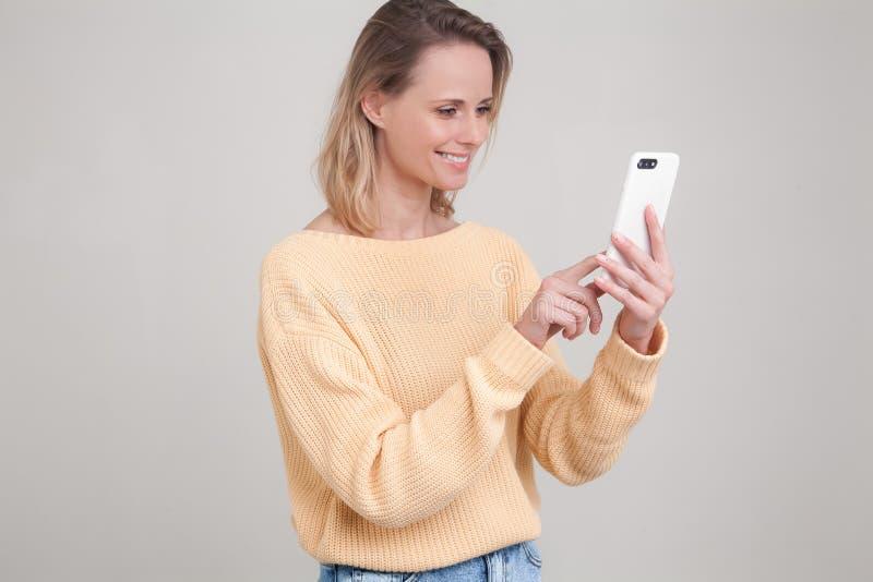 使用手机,传讯的年轻白肤金发的微笑的妇女画象,是愉快与她的男朋友聊天 r 库存照片