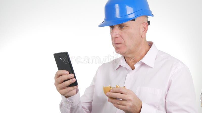 使用手机,工程师图象吃三明治和文本 免版税图库摄影