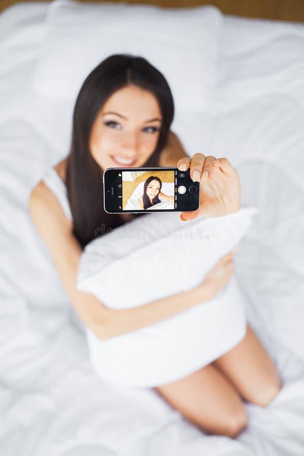 使用手机,愉快的逗人喜爱的妇女射击在床上说谎 图库摄影