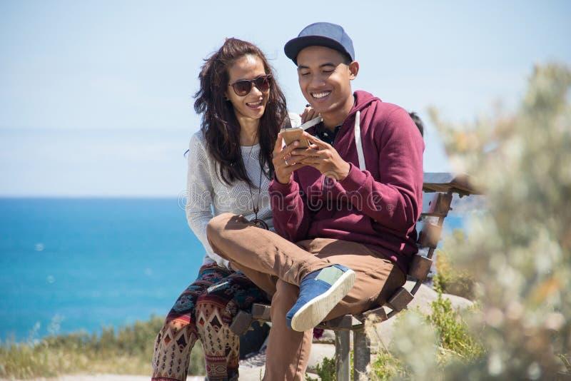 使用手机,愉快的年轻夫妇一起 免版税库存照片