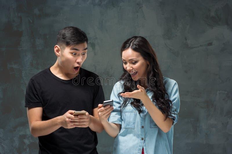 使用手机,特写镜头画象的亚洲年轻夫妇 免版税库存图片