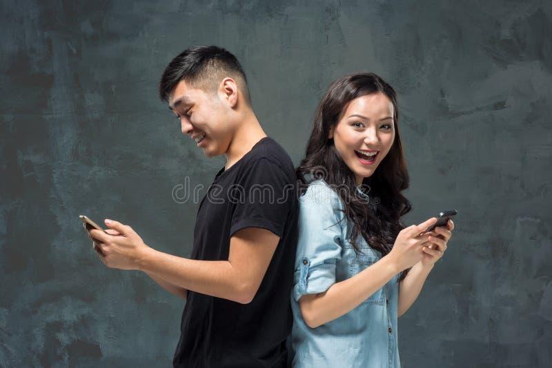 使用手机,特写镜头画象的亚洲年轻夫妇 库存图片