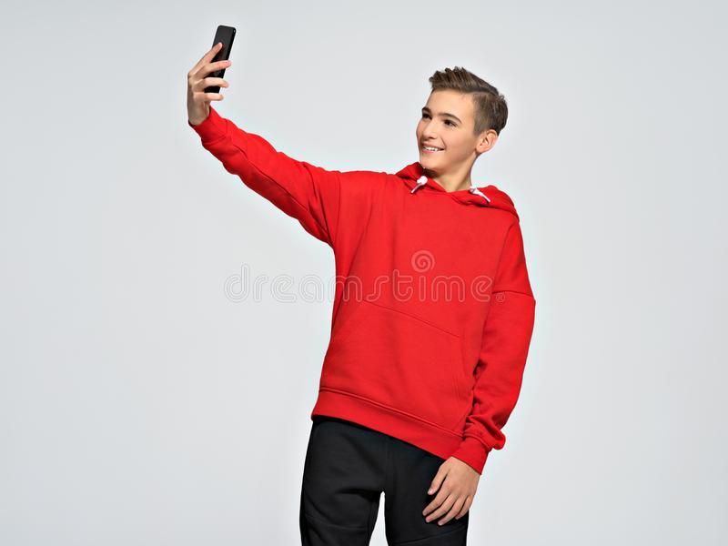 使用手机,英俊的少年做selfie 库存图片