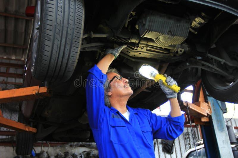 使用手电的汽车修理师审查的汽车在自动修理服务中 免版税库存图片