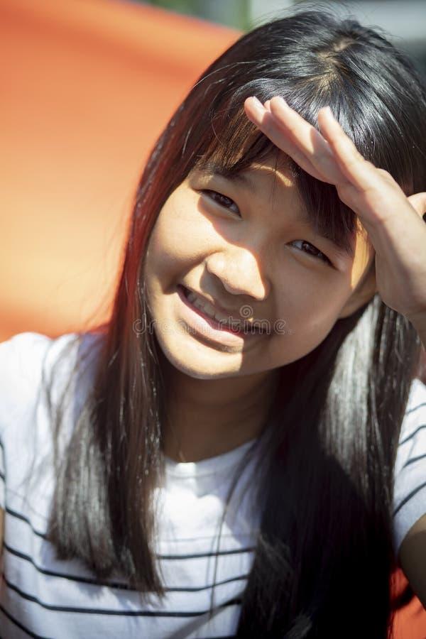 使用手的Tan皮肤亚裔少年保护在面孔烧的太阳sk 图库摄影