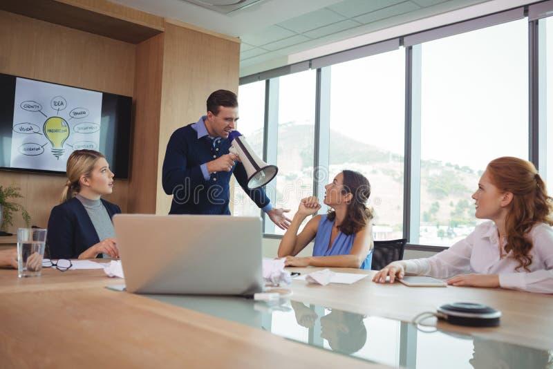使用扩音机的恼怒的商人在会议室 免版税库存图片