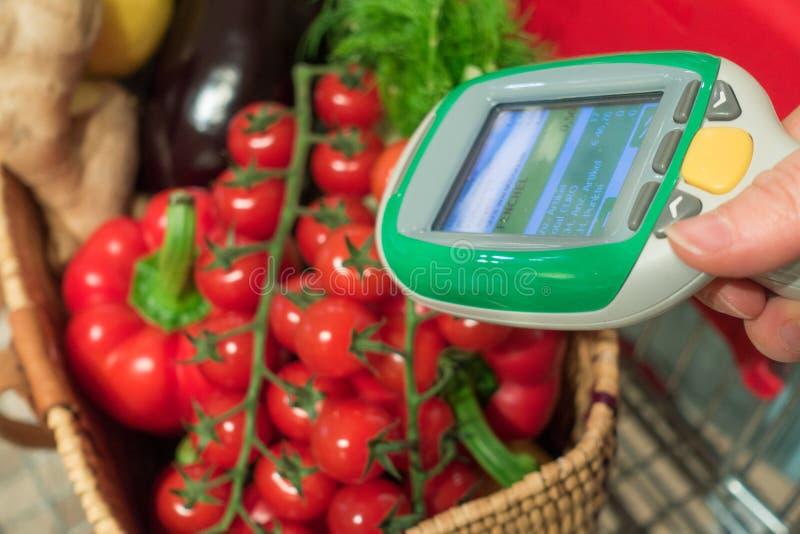 使用扫描器设备的妇女顾客在超级市场 自动物体识别 免版税库存照片