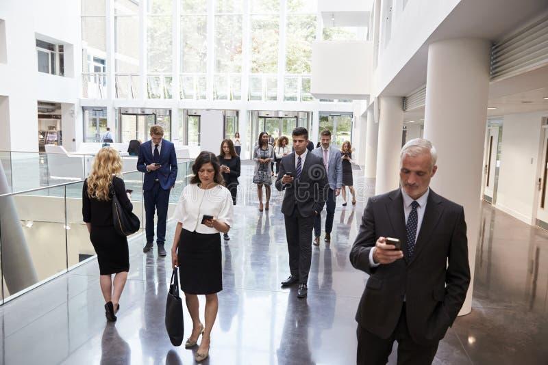 使用技术的买卖人在办公室繁忙的大厅地区  免版税库存照片