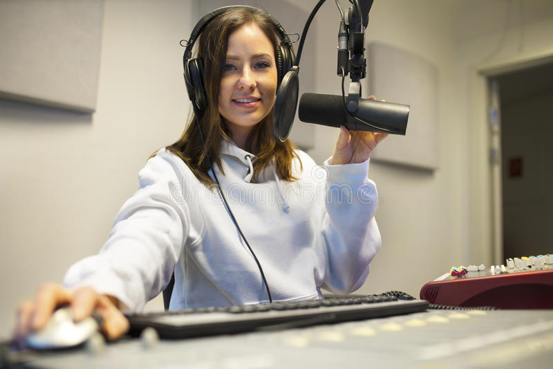 使用技术的确信的女性骑师在无线电演播室 库存照片