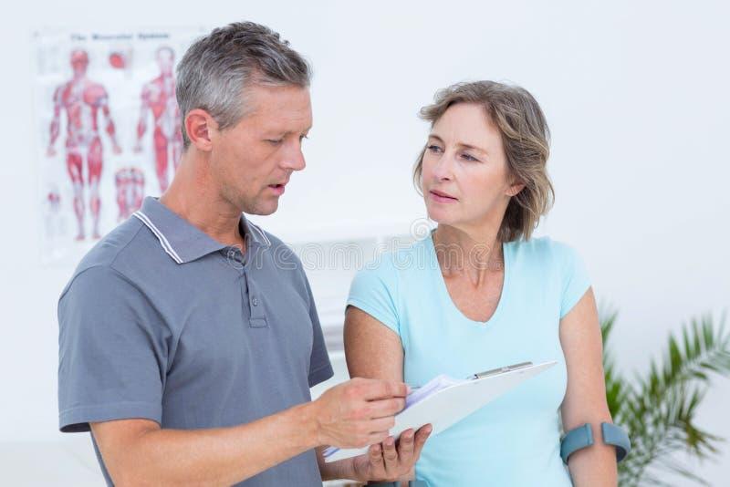 使用拐杖的妇女和谈话与她的医生 免版税库存照片